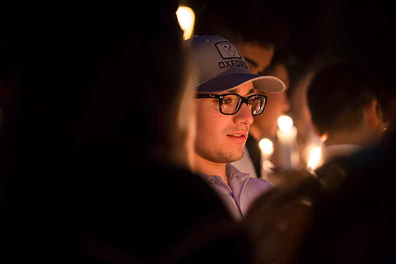 A student takes part in the candelight procession as part of Convocation.