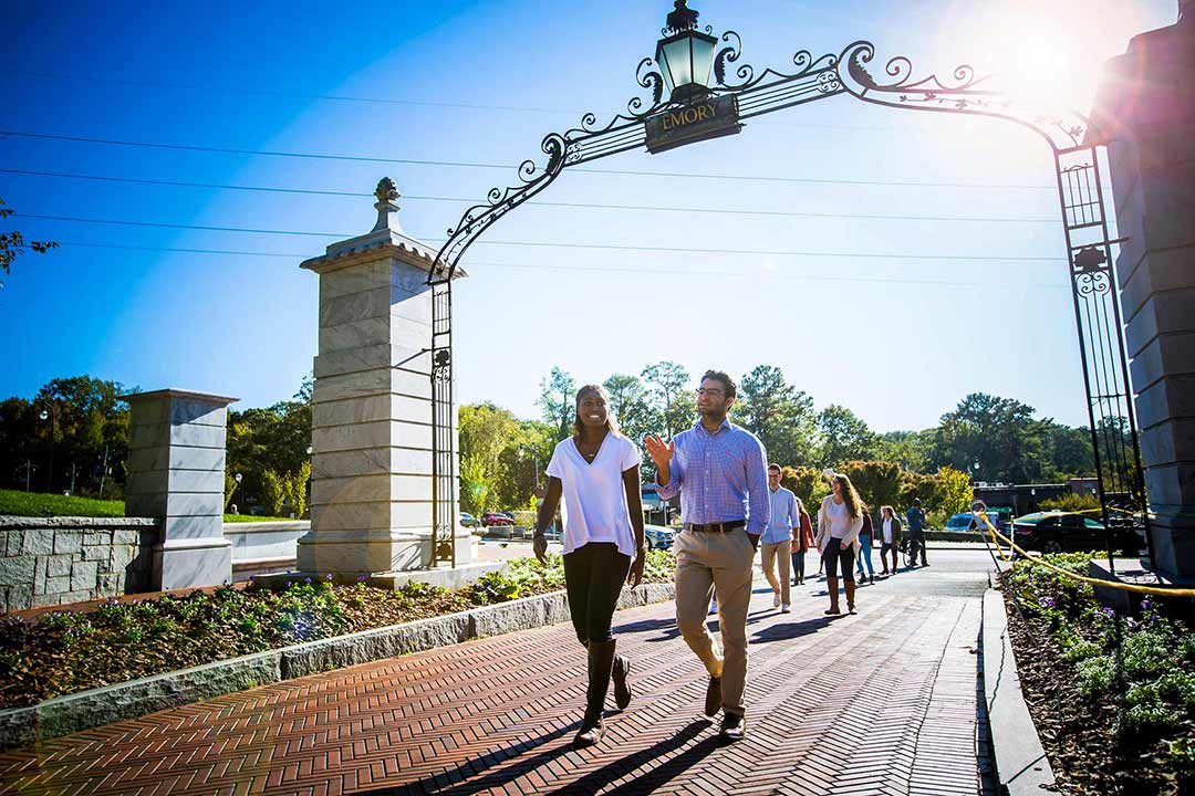 Students walk through Emory's entrance gate.