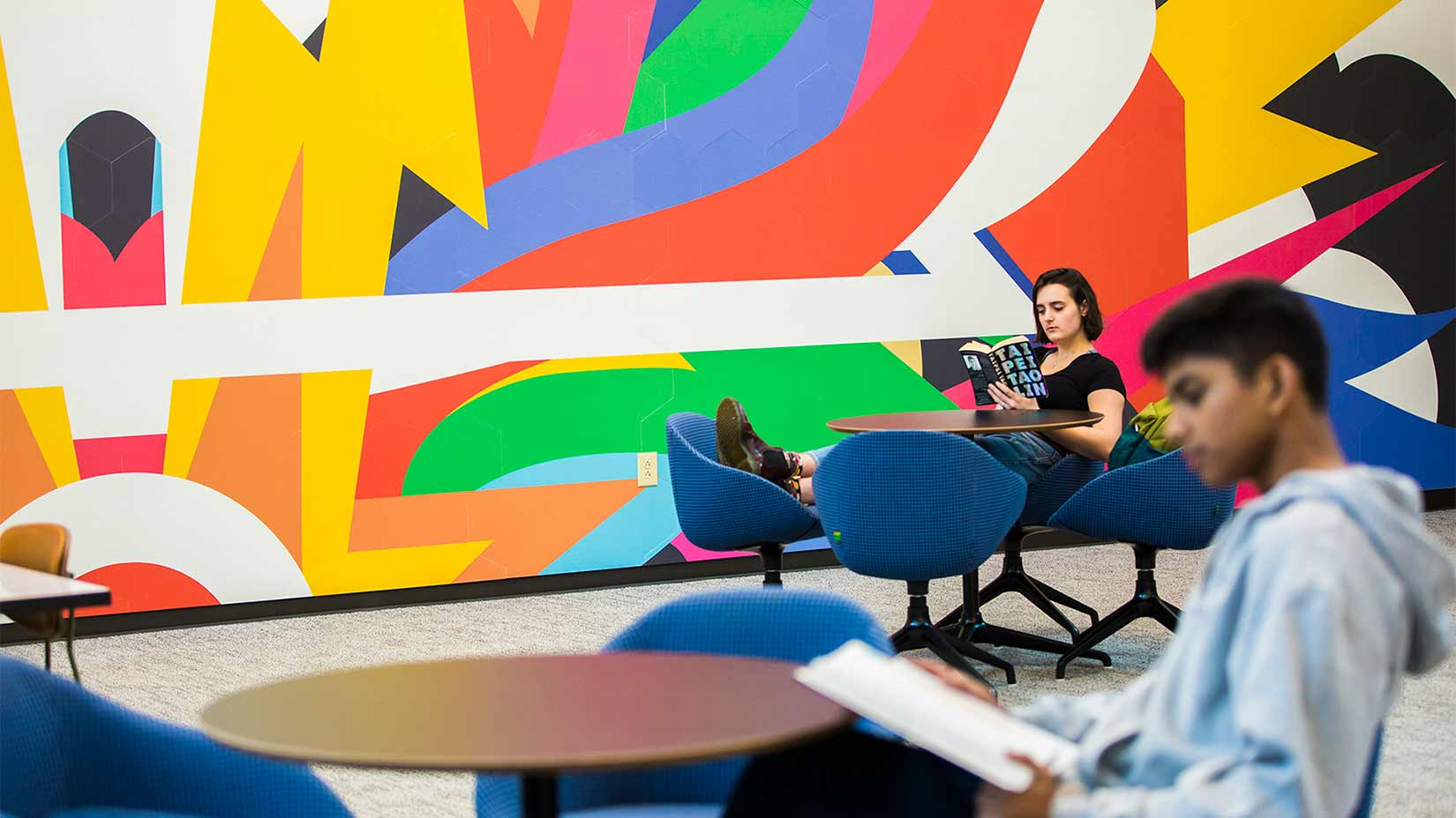Students relax in the mural room of the student center.