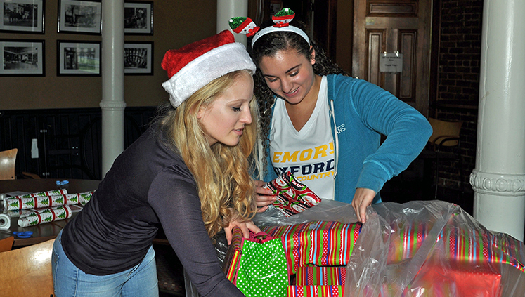 Oxford students wrap gifts during a party with presents provided by faculty and staff for children in the surrounding community.