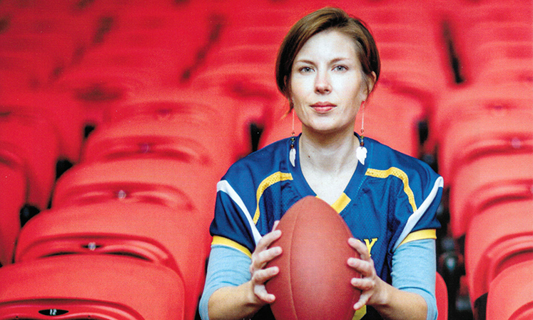 Erin Tarver poses with a football